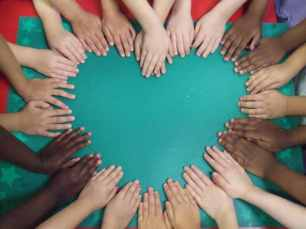 People of different backgrounds placing their hands together to form a heart.
